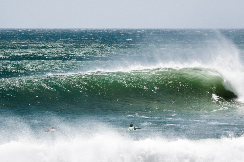 surfers paddling out to powerful surf